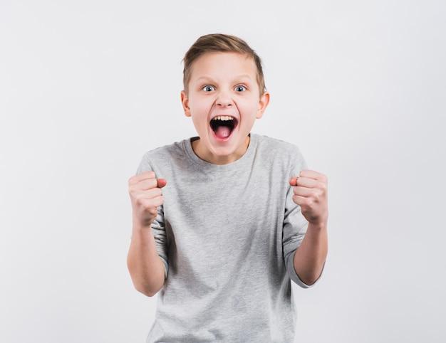 白い背景に対して立っている彼の拳を噛みしめて興奮している少年