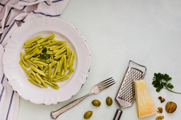 Паста шпинат джемелли на белой керамической тарелке с ингредиентами на белом фоне