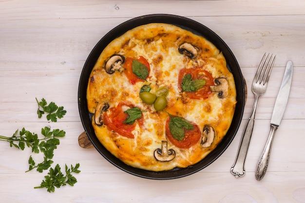トマトと新鮮なキノコとオリーブの木製の背景においしいピザ