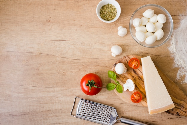 Стеклянная миска с сыром моцарелла; томаты; блок с базиликом и сыром с теркой на столе