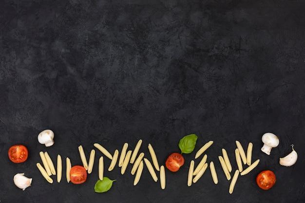 半分にしたトマトの生ガルガネッリパスタキノコ;黒のテクスチャ背景の下にニンニクとバジル
