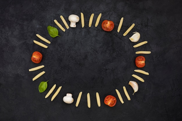 未調理のガルガネリパスタで作られた空の円形フレーム。トマト;キノコ;ニンニクとバジルの黒の織り目加工の背景