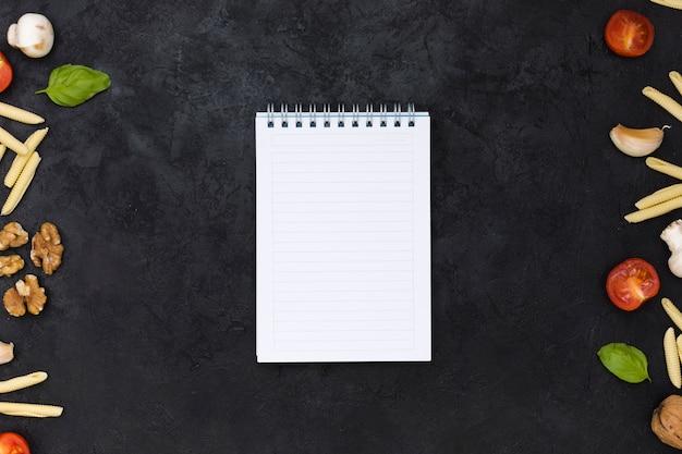 黒の背景の側にピザ成分を持つ単一行空白スパイラルメモ帳