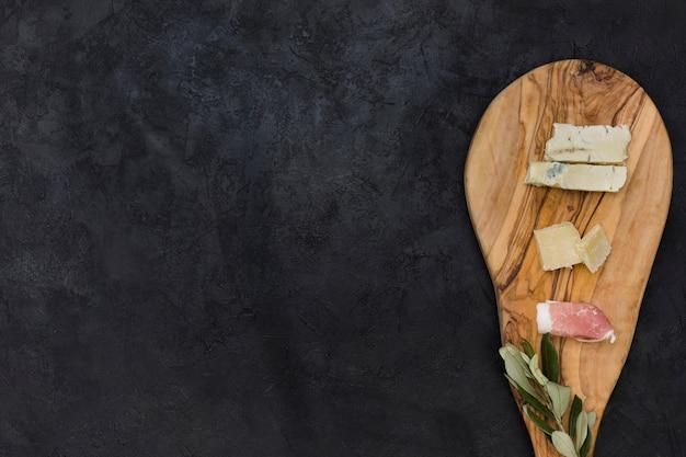 チーズの俯瞰。黒の背景上のまな板にベーコンとオリーブの小枝