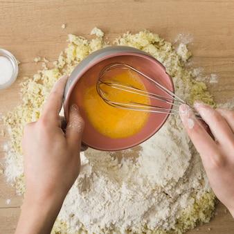 イタリアのニョッキを準備するためのおろしチーズと小麦粉にホイップエッグを注ぐ人の手のクローズアップ