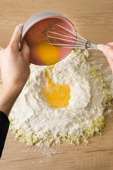 Рука человека наливает взбитые яйца в муку и тертый сыр для приготовления итальянских клецок на деревянный стол