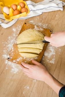 木製の机の上のイタリアのニョッキパスタを準備するためのナイフで生地を切る女性の手