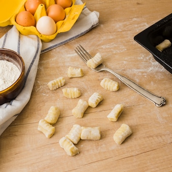 小麦粉と卵の木製のテーブルの上のフォークと調理の自家製ポテトニョッキ