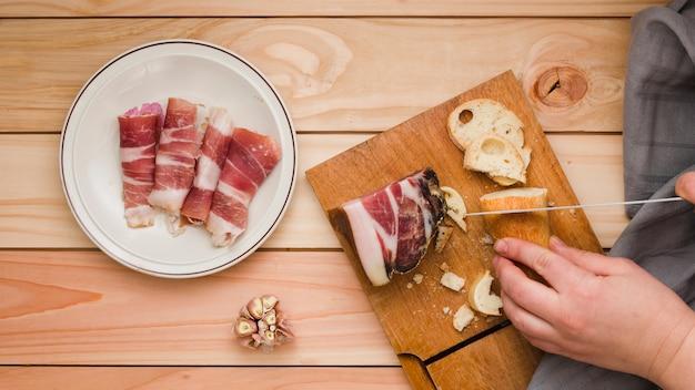 木製のテーブルの上の白い皿にロールアップしたベーコンとパンのスライスを切る人のクローズアップ