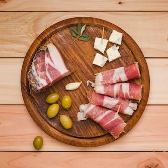 Оливки; зубчик чеснока; ломтик сыра и бекон на деревянный поднос на столе