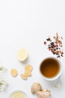 Имбирь; лимон; травяной чай с сушеными травами и цветком жасмина на белом фоне