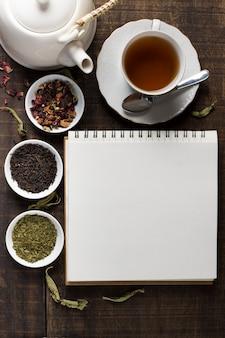 ティーポットと空白のスパイラルメモ帳。ティーカップと木製の机の上の白いボウルにハーブティーのボウル