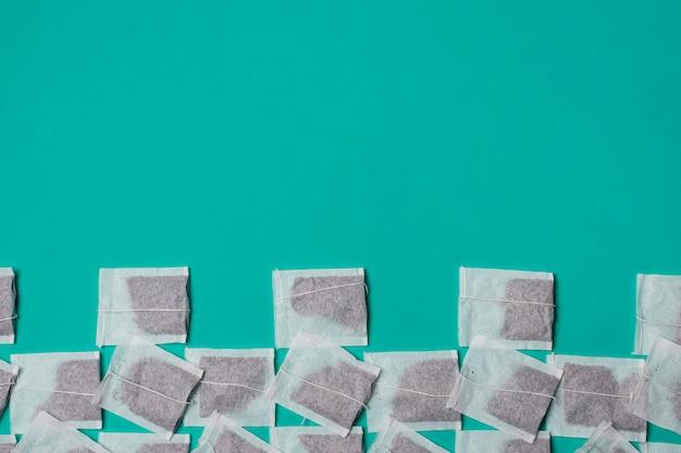 Поднятый вид белого чая в пакетиках на зеленом фоне