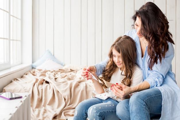 母とかわいい娘のグリーティングカードを読む