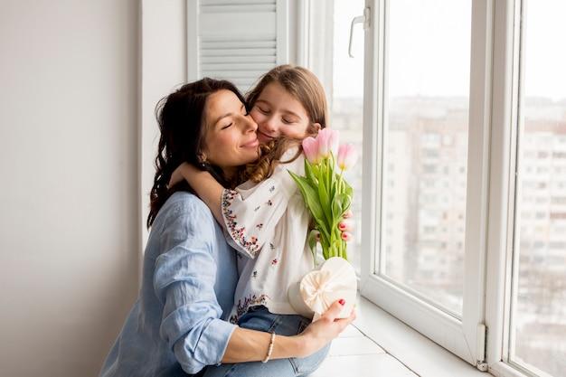 Мать с цветами обнимает дочь