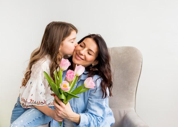 Дочь с тюльпанами целует маму в щеку