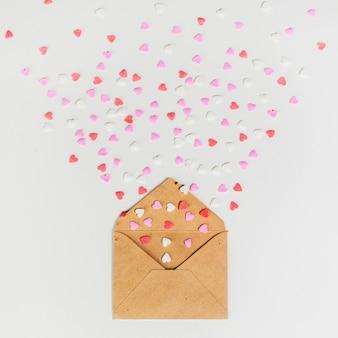 白いテーブルの上の小さな紙のハートの封筒