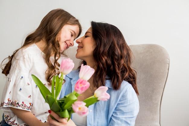 Дочь с тюльпанами обнимает маму в кресле