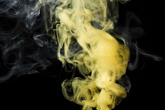黒の背景に黄色の煙のクローズアップ
