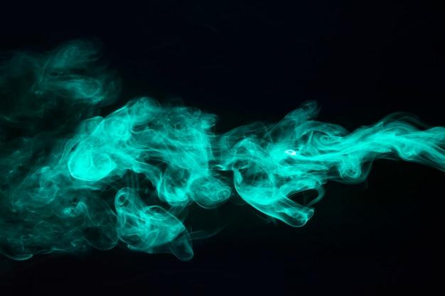 黒の背景にターコイズブルーの煙