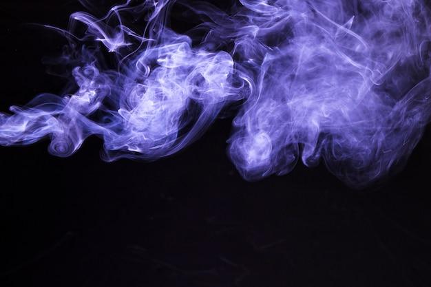 黒い背景に柔らかい紫色の煙の動き