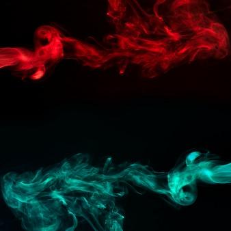 黒の暗い背景に抽象的な赤と青緑色の煙