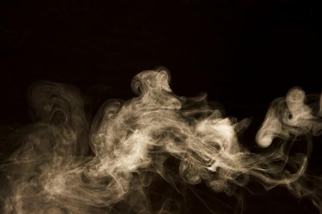 黒の背景に抽象的な白い煙