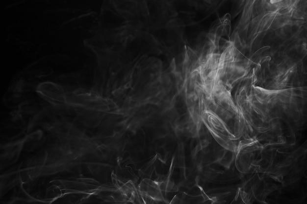 黒い背景に対して周りに渦巻く煙