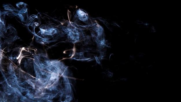 黒の背景に滑らかに煙を吹く