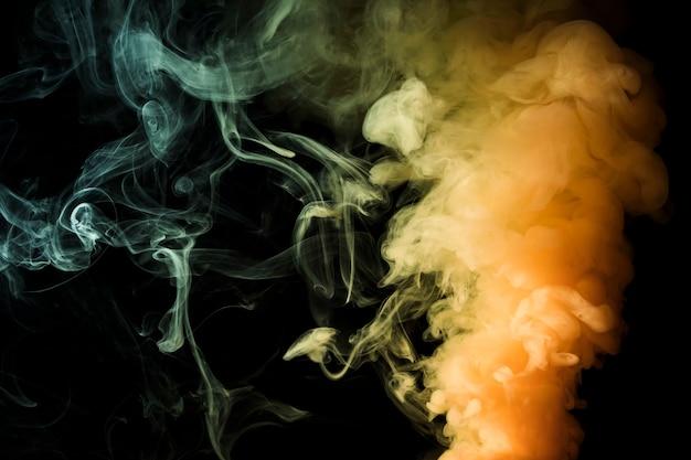 煙の抽象的な黒い背景の黄色の濃いヒューム