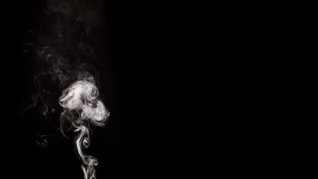 黒い背景に白い煙の渦巻き模様