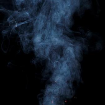 着色された煙が黒の背景に広がる