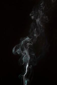 黒い背景に白い煙のオーバーレイを吹く