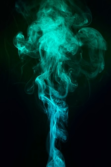 青と緑の煙が黒い背景に広がる