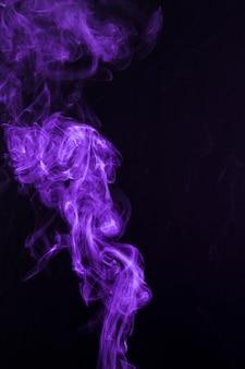 黒の背景に紫の旋回煙