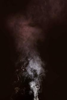 黒の背景に吹く白い煙