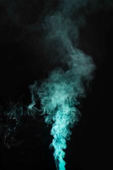 暗い背景に緑色の煙の動き