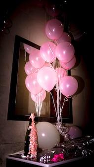 机の上のピンクの風船でシャンパンのボトルのクローズアップ