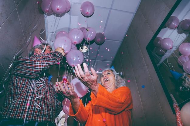 パーティーで紙吹雪を投げるシニアの幸せなカップルの低角度のビュー