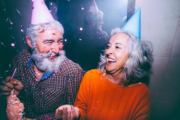 年配のカップルが誕生日パーティーを楽しんでいる頭の上のパーティーハットを着て
