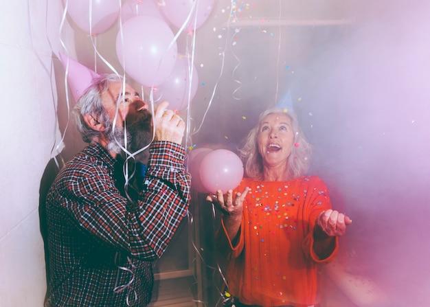 パーティーホーンを吹く男と女が空気で紙吹雪を投げる