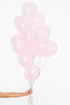 白い背景にピンクの風船の束を持っている手のクローズアップ