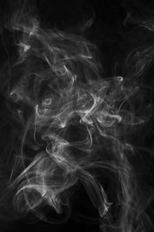 黒の背景に滑らかに吹く煙