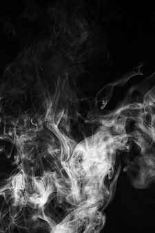 黒の背景に吹く霧の煙