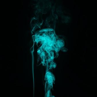 明るい青緑色の煙の道の抽象的な黒の背景