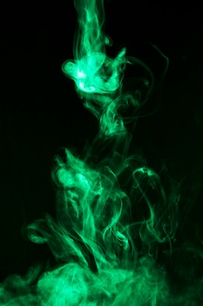 黒の背景に明るい緑の煙の動き
