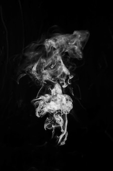 黒い背景の中央に白い煙