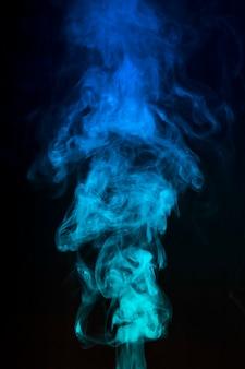 青い色の煙が黒の背景に広がる