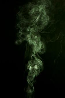 黒の背景に緑の煙の影響
