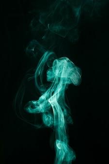 Вихрь зеленого дыма движется на черном фоне
